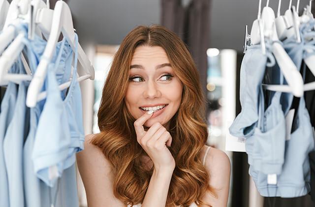 Kobieta rozmyślająca jakie ubrania wyciągnąć z szafy na wymiar