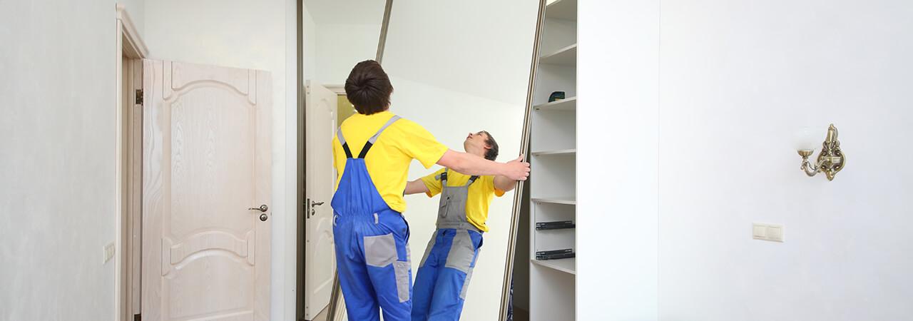 Pracownik montujący drzwi przesuwne do szafy na wymiar