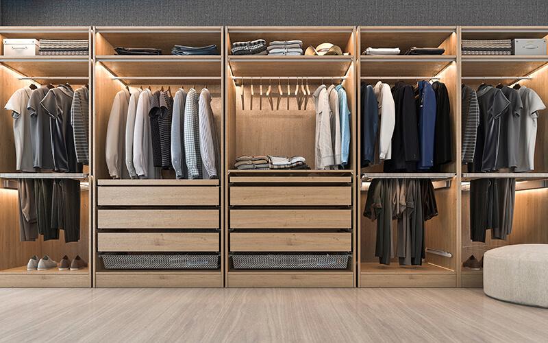 Ogromna uzupełniona garderoba z szufladami i drążkami na ubrania w kolorze jasnego drewna