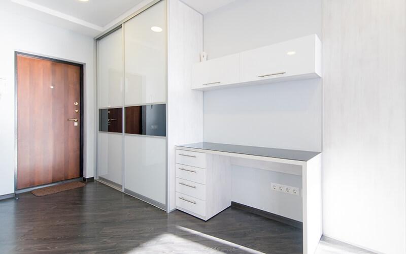 Biało szafa na wymiar z białymi drzwiami przesuwnymi z czarnym paskiem obok biurka w pokoju dziecięcym