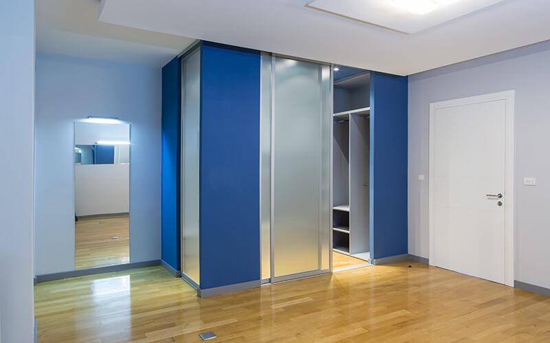 Szafa z drzwiami przesuwnymi w przedpokoju z niebieskimi wstawkami i malowaniem
