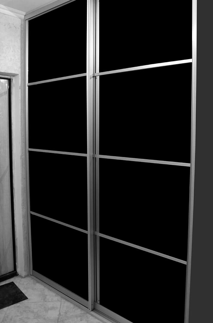 Szafa przesuwna z czarnymi drzwiami przesuwnymi firmy indeco