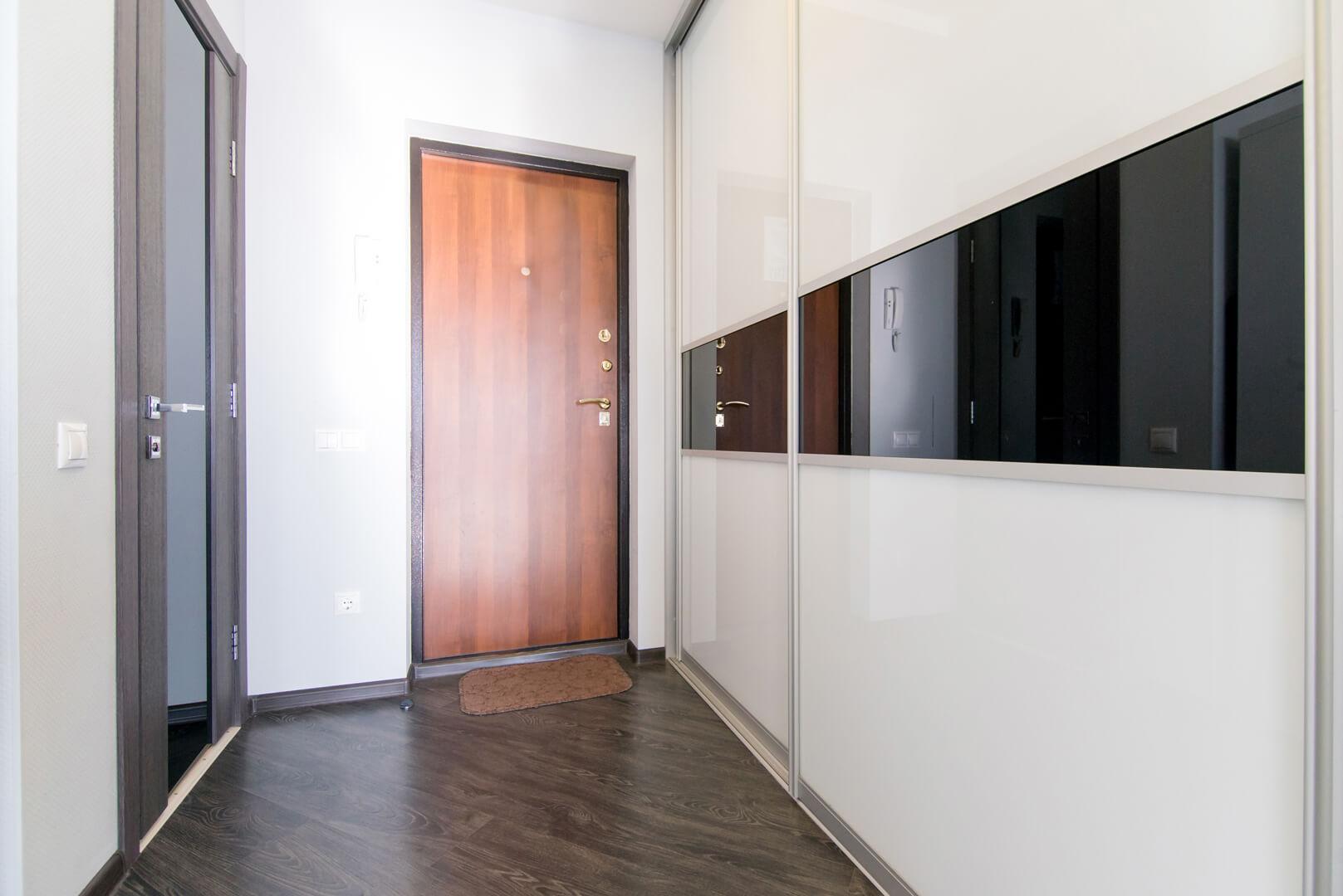Szafa na wymiar z szklanymi biało czarnymi drzwiami przesuwnymi w przedpokoju