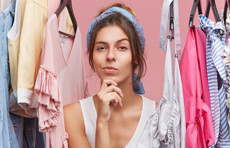 Kobieta znajdująca się pomiędzy zawieszonymi ubraniami