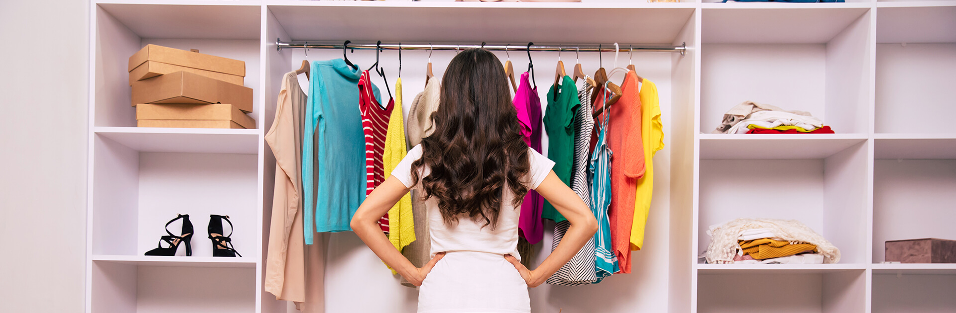 Kobieta stojąca przed szafą, zastanawiająca się w co się ubrać