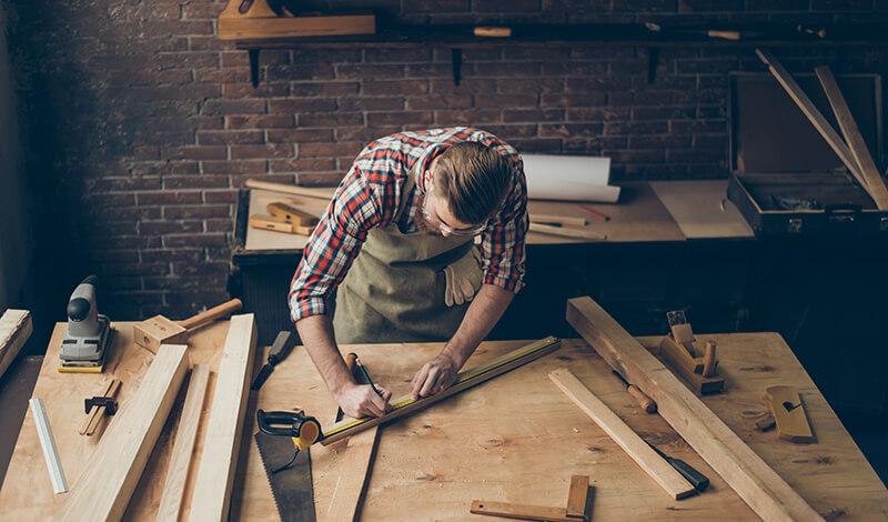 Stolarz wymierza długości drewna