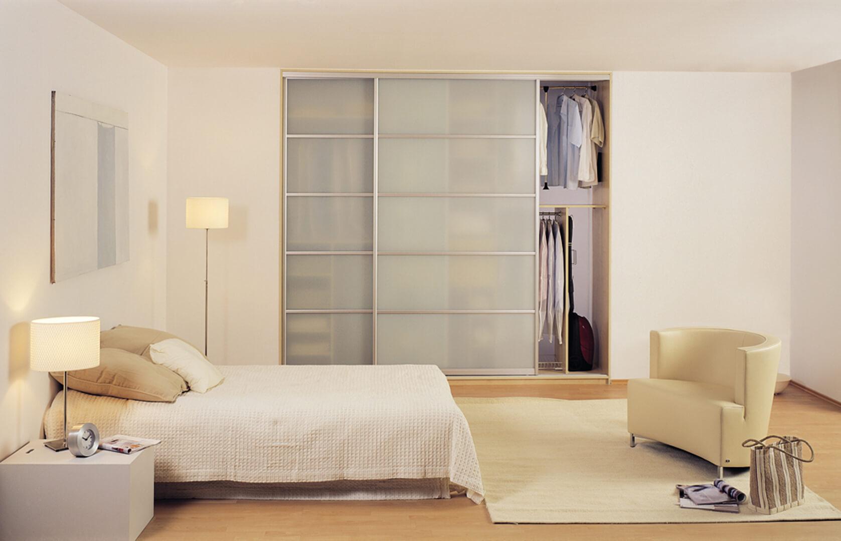 Szafa przesuwna z szklanymi drzwiami przesuwnymi firmy INDECO Wybrzeże w sypialni