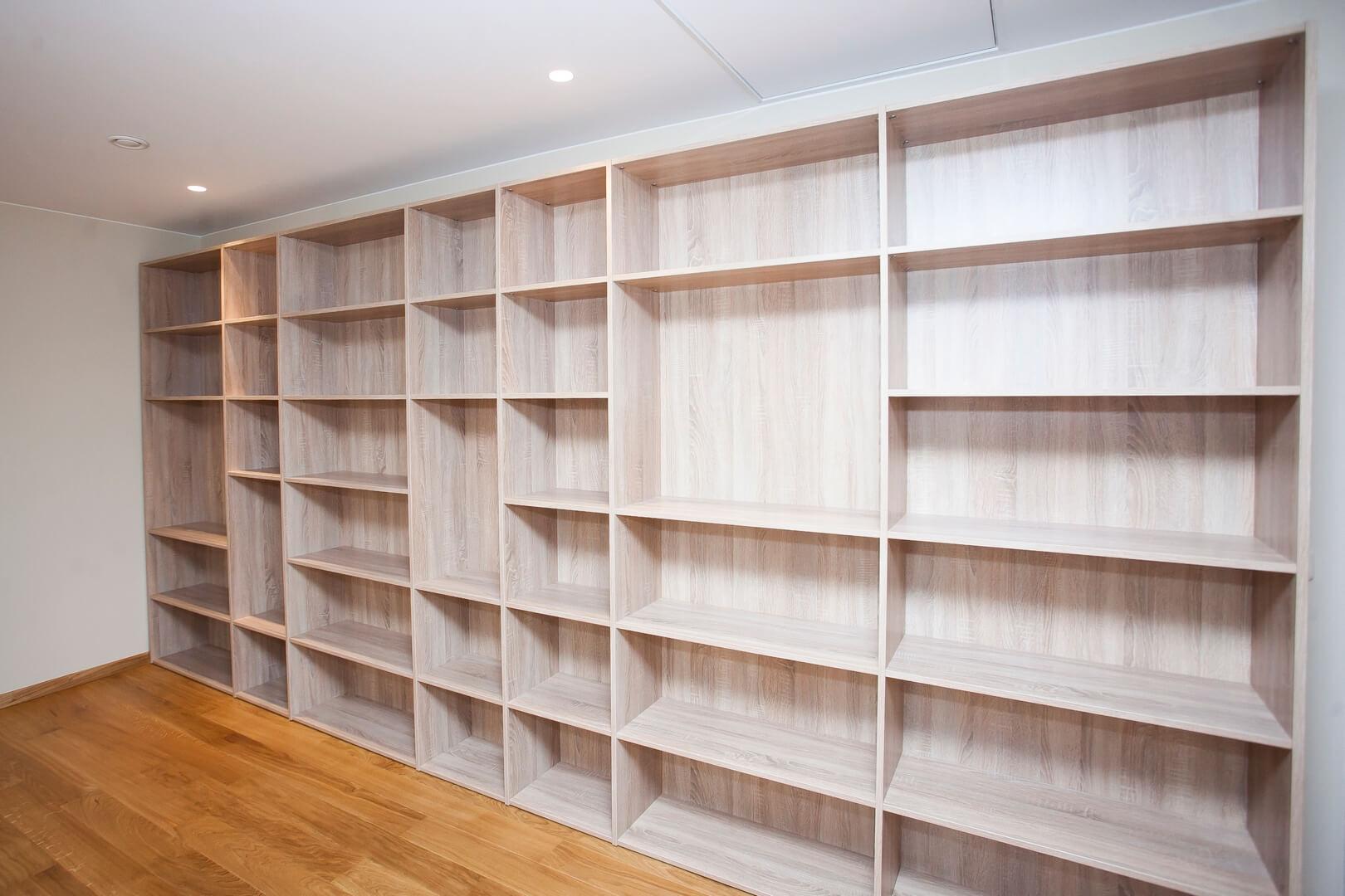Wnętrze drewnianej szafy rozciągniętej na całą długość ściany w pokoju