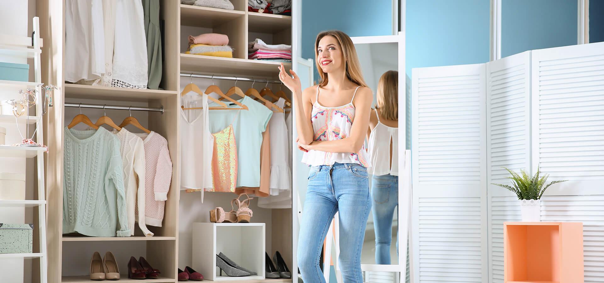 Uśmiechnięta dziewczyna stojąca przy szafie na wymiar