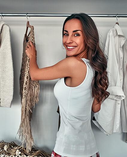 Uśmiechnięta kobieta wyjmująca ubrania z szafy na wymiar